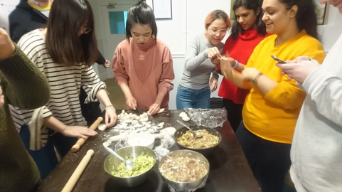 A group of women cooking in a kitchen preparing food  Description automatically generated